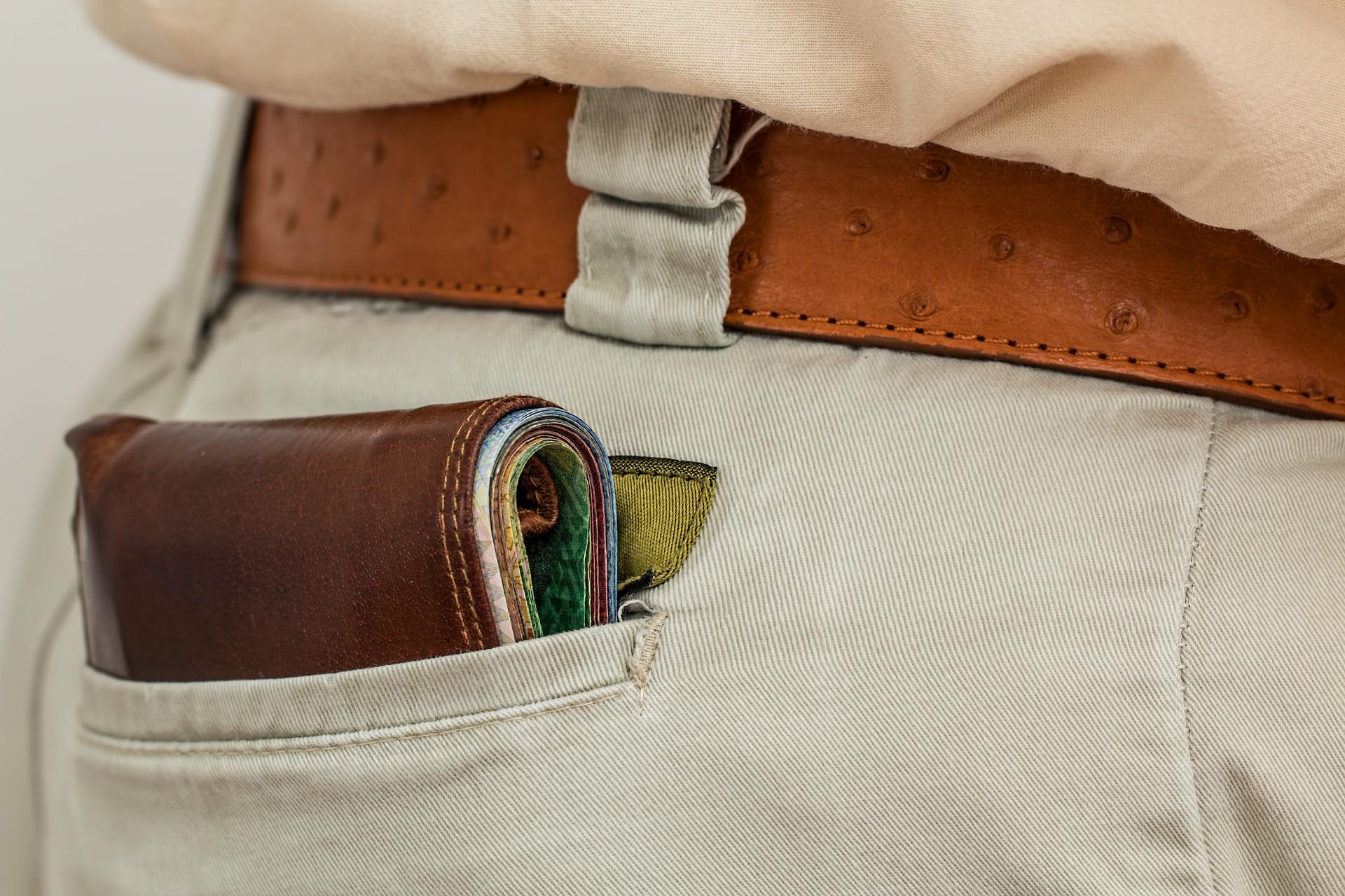 Person med plånbok som sticker upp ur bakfickan.
